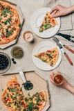 Άποψη κινηματογραφήσεων σε πρώτο πλάνο της γυναίκας που έχει το γεύμα με την πίτσα και το ποτό Στοκ Φωτογραφία