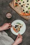 Άποψη κινηματογραφήσεων σε πρώτο πλάνο της γυναίκας που κόβει μια φέτα της πίτσας στοκ εικόνα με δικαίωμα ελεύθερης χρήσης