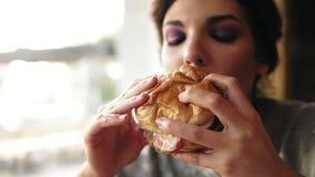 Άποψη κινηματογραφήσεων σε πρώτο πλάνο της νέας γυναίκας που δαγκώνει μεγάλο νόστιμο burger στον καφέ Σε αργή κίνηση πυροβολισμός απόθεμα βίντεο