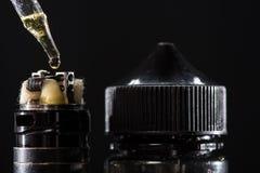 Άποψη κινηματογραφήσεων σε πρώτο πλάνο της πλήρωσης του ηλεκτρονικού τσιγάρου με το ε-υγρό στοκ εικόνες