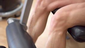 Άποψη κινηματογραφήσεων σε πρώτο πλάνο του αθλητή ατόμων με τα μυϊκά πόδια που επιλύει στον εκπαιδευτή μπουκλών ποδιών γυμναστική φιλμ μικρού μήκους