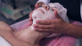 Άποψη κινηματογραφήσεων σε πρώτο πλάνο του επαγγελματικού cosmetologist που η ειδική μάσκα στο πρόσωπο και το λαιμό γυναικών ` s  απόθεμα βίντεο