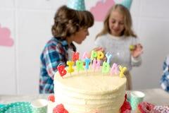 άποψη κινηματογραφήσεων σε πρώτο πλάνο του εύγευστου κέικ γενεθλίων στον εορταστικό πίνακα και τα ευτυχή παιδιά Στοκ εικόνες με δικαίωμα ελεύθερης χρήσης