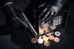 Άποψη κινηματογραφήσεων σε πρώτο πλάνο του ληστή με το πυροβόλο όπλο που κλέβει bitcoin στοκ φωτογραφία με δικαίωμα ελεύθερης χρήσης