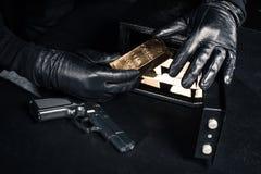 Άποψη κινηματογραφήσεων σε πρώτο πλάνο του ληστή με το πυροβόλο όπλο που παίρνει τους χρυσούς φραγμούς στοκ φωτογραφία