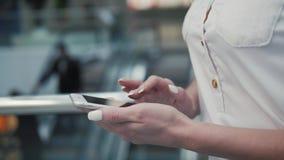 Άποψη κινηματογραφήσεων σε πρώτο πλάνο του νέου ελέγχου γυναικών stats στο κινητό τηλέφωνό της τελική λεωφόρος αγορών αερολιμένων απόθεμα βίντεο