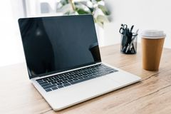 άποψη κινηματογραφήσεων σε πρώτο πλάνο του lap-top με την κενή οθόνη, το φλυτζάνι καφέ και τα χαρτικά στοκ φωτογραφία με δικαίωμα ελεύθερης χρήσης