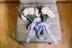 Άποψη κινηματογραφήσεων σε πρώτο πλάνο των ανθοδεσμών twoo των άσπρα τριαντάφυλλων και lavender που τυλίγονται με τις κορδέλλες Στοκ φωτογραφία με δικαίωμα ελεύθερης χρήσης