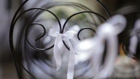 Άποψη κινηματογραφήσεων σε πρώτο πλάνο των γαμήλιων καρεκλών που διακοσμούνται με τα άσπρα τόξα φιλμ μικρού μήκους