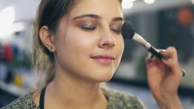 Άποψη κινηματογραφήσεων σε πρώτο πλάνο των επαγγελματικών χεριών καλλιτεχνών ` s makeup που εφαρμόζει το του προσώπου blusher στο φιλμ μικρού μήκους