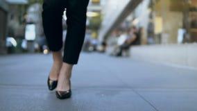 Άποψη κινηματογραφήσεων σε πρώτο πλάνο των θηλυκών ποδιών που περπατούν μέσω του στο κέντρο της πόλης Επιχειρηματίας που φορά τα  φιλμ μικρού μήκους