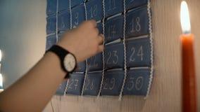 Άποψη κινηματογραφήσεων σε πρώτο πλάνο των θηλυκών χεριών που παίρνουν έξω την κάρτα από το ημερολόγιο εμφάνισης με τα δώρα Ατμόσ φιλμ μικρού μήκους