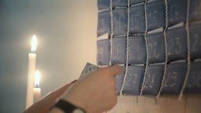 Άποψη κινηματογραφήσεων σε πρώτο πλάνο των θηλυκών χεριών που παίρνουν έξω την κάρτα από το ημερολόγιο εμφάνισης με τα δώρα και π φιλμ μικρού μήκους