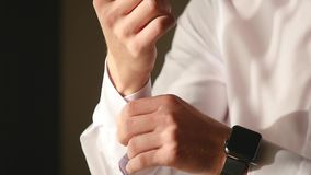 Άποψη κινηματογραφήσεων σε πρώτο πλάνο των νέων αρσενικών χεριών που παίρνουν ντυμένων στο πρωί Το άτομο κουμπώνει τις μανσέτες σ απόθεμα βίντεο