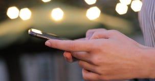 Άποψη κινηματογραφήσεων σε πρώτο πλάνο των χεριών που δακτυλογραφούν στο τηλέφωνο κυττάρων με τα φω'τα στο υπόβαθρο απόθεμα βίντεο