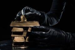 Άποψη κινηματογραφήσεων σε πρώτο πλάνο των χρυσών φραγμών και bitcoin στα χέρια στοκ εικόνα