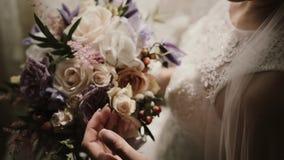 Άποψη κινηματογραφήσεων σε πρώτο πλάνο νέου φωτεινού με τη γαμήλια ανθοδέσμη Η γυναίκα κοιτάζει και αγγίζει τη φυσική σύνθεση λου απόθεμα βίντεο