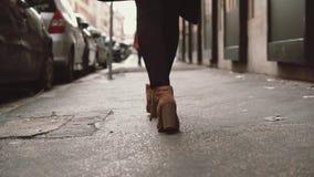 Άποψη κινηματογραφήσεων σε πρώτο πλάνο του μοντέρνου περπατήματος γυναικών σε λίγη οδό Το κορίτσι που φορά τα παπούτσια στα τακού φιλμ μικρού μήκους