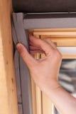 Άποψη κινηματογραφήσεων σε πρώτο πλάνο του χεριού ατόμων που κρατά ένα στρώμα μόνωσης στο παράθυρο στεγών dormer ή το φεγγίτη στοκ φωτογραφίες