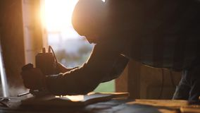 Άποψη κινηματογραφήσεων σε πρώτο πλάνο των ατόμων που εργάζονται με το ηλεκτρικό τορνευτικό πριόνι και την ξύλινη σανίδα φλόγα ήλ απόθεμα βίντεο
