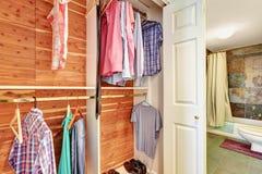 Άποψη κινηματογραφήσεων σε πρώτο πλάνο των ενδυμάτων και των πουκάμισων στα ξύλινα υπόστεγα σε ένα ντουλάπι Στοκ φωτογραφίες με δικαίωμα ελεύθερης χρήσης