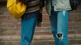 Άποψη κινηματογραφήσεων σε πρώτο πλάνο των ποδιών νεαρών άνδρων και γυναικών που φορούν τα τζιν Ζεύγος Hipster με το σακίδιο πλάτ φιλμ μικρού μήκους