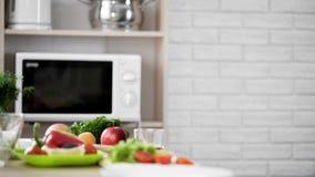 Άποψη κουζινών με το φούρνο μικροκυμάτων και τα φρέσκα λαχανικά και τα φρούτα στον πίνακα Στοκ φωτογραφίες με δικαίωμα ελεύθερης χρήσης