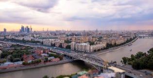 Άποψη κλίσης και μετατόπισης του πανοράματος ηλιοβασιλέματος της Μόσχας με τα ρόδινα σύννεφα, γέφυρα, διακινούμενες βάρκες Στοκ Εικόνες