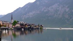 Άποψη λιμνών ξημερωμάτων με τις εκκλησίες Hallstatt στα όρη της Αυστρίας με τα παραδοσιακά κτήρια, τα βουνά και τις βάρκες επάνω απόθεμα βίντεο