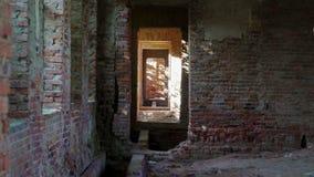 Άποψη μέσω της πόρτας στο στενό διάδρομο με το ηλιοφώτιστο μπάλωμα στο γυμνό τοίχο πετρών απόθεμα βίντεο