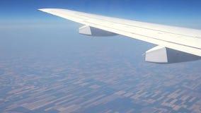 Άποψη μέσω του παραθύρου αεροπλάνων - φτερό αεροπλάνων που κινείται επάνω από τους τομείς φιλμ μικρού μήκους