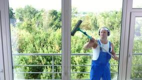 Άποψη μέσω του παραθύρου, όμορφος άνδρας εργαζόμενος της καθαρίζοντας υπηρεσίας, στις μπλε φόρμες, με τα ακουστικά, καθαρισμός, π φιλμ μικρού μήκους