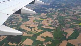 Άποψη μέσω του φωτιστικού των αεροσκαφών στο έδαφος, που πετά σε ένα αεροπλάνο πέρα από τους γεωργικούς τομείς απόθεμα βίντεο