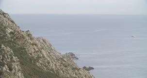 Άποψη μιας βάσης απότομων βράχων με τη θάλασσα στον ορίζοντα και μια ναυσιπλοΐα βαρκών απόθεμα βίντεο
