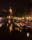 Άποψη μιας εκκλησίας και ενός καναλιού στο Άμστερνταμ, Κάτω Χώρες τη νύχτα Η βασιλική Άγιου Βασίλη sint-Nicolaasbasiliek με το ρ Στοκ Εικόνες