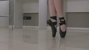 Άποψη μιας στάσης ballerina EN pointe στις άκρες των toe της ανά ένα ζευγάρι των παπουτσιών μπαλέτου φιλμ μικρού μήκους