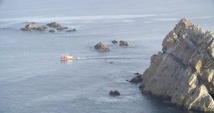 Άποψη μιας στέλνοντας βάρκας που ξεπερνά έναν σχηματισμό των βράχων φιλμ μικρού μήκους