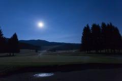 Άποψη νύχτας με το φεγγάρι του γηπέδου του γκολφ στο δάσος Cansiglio Στοκ Εικόνες