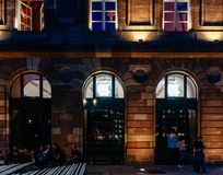 Άποψη νύχτας προσόψεων της Apple Store με τους ανυπόμονους πελάτες που περιμένουν στη σειρά αναμονής Στοκ Εικόνες