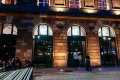 Άποψη νύχτας προσόψεων της Apple Store με τους ανυπόμονους πελάτες που περιμένουν στη σειρά αναμονής Στοκ εικόνες με δικαίωμα ελεύθερης χρήσης