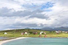 Άποψη πέρα από ένα νορβηγικό φιορδ σε ένα νησί με την αλιεία των καλυβών και του ρ στοκ εικόνες