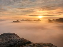 Άποψη πέρα από την αιχμηρή άκρη ψαμμίτη στο μακροχρόνιο σύνολο κοιλάδων της πρώτης φθινοπωρινής υδρονέφωσης η misty δασική κοιλάδ Στοκ Φωτογραφία