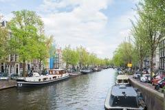 Άποψη πέρα από το ολλανδικό κανάλι με τις βάρκες, τις προσόψεις σπιτιών και τα πράσινα δέντρα Στοκ Εικόνα