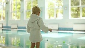 Άποψη πίσω πλευρών ενός μικρού αγοριού στο μπουρνούζι που ρίχνει τις σφαίρες και από τα δύο χέρια στην πισίνα Εύθυμος Έξω από απόθεμα βίντεο