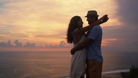 Άποψη πίσω πλευρών, ζεύγος των εραστών που εξετάζουν το όμορφο ηλιοβασίλεμα, αγκάλιασμα, σε αργή κίνηση φιλμ μικρού μήκους