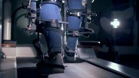 Άποψη πίσω πλευρών των ποδιών στη μέση μιας συνόδου φυσιοθεραπείας για έναν προσομοιωτή περπατήματος απόθεμα βίντεο