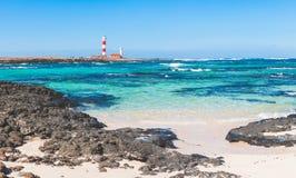 Άποψη παραλιών σε Fuerteventura με το σαφείς νερό και το φάρο Στοκ Φωτογραφία