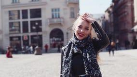 Άποψη περιστροφής ενός νέου ελκυστικού ξανθού κοριτσιού με τα κόκκινα κραγιόν, και περιστασιακό σακάκι δέρματος που έχει έναν περ απόθεμα βίντεο