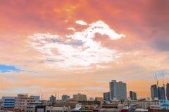 Άποψη πουλιών πέρα από τη εικονική παράσταση πόλης με το ηλιοβασίλεμα και τα σύννεφα το βράδυ Γ Στοκ Εικόνες