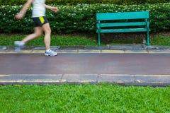 Άποψη ποδιών Jogging ενάντια σε έναν πράσινο πάγκο Στοκ Εικόνες